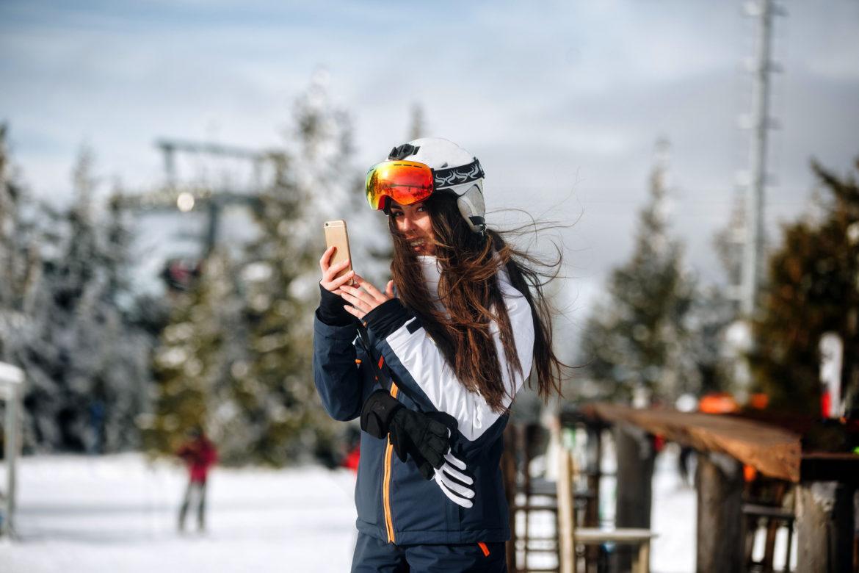 frau im skigebiet mit smartphone